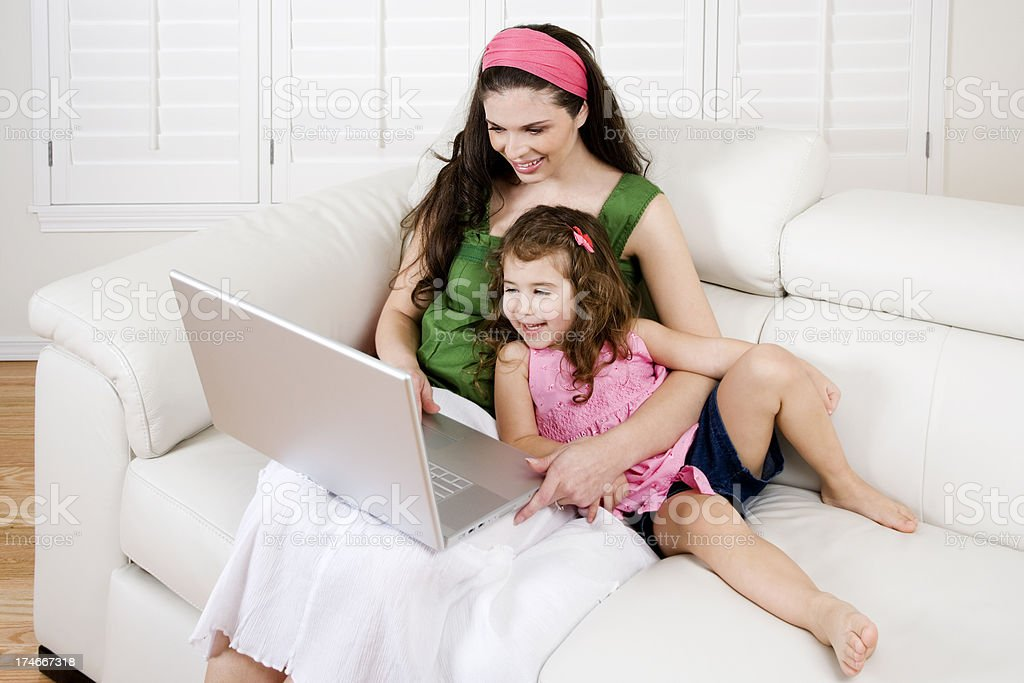 Hispanic Mother daughter playing computer home white leather couch interior royalty-free stock photo
