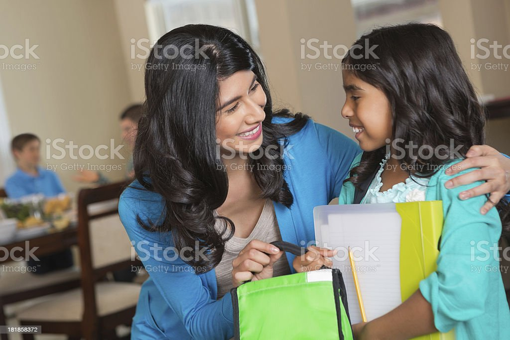 Hispanic mother helping daughter get ready for school royalty-free stock photo