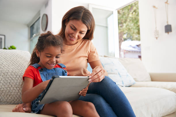 Hispanic Mother Helping Daughter To Home School And Do Homework  With Digital Tablet stock photo