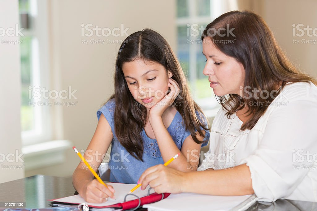 Hispanic mother helping daughter with homework stock photo