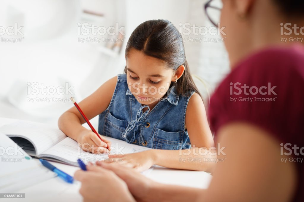 Hispanic Mother Helping Girl Doing School Homework At Home stock photo