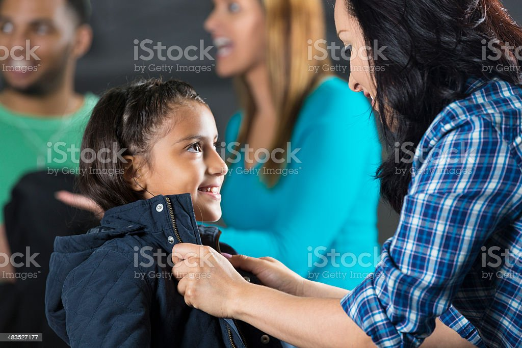 Hispanic mother selecting coat for daughter at winter clothing drive stock photo