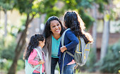 A mature Hispanic woman in her 40s standing with her two young daughters, 4 and 6 years old, holding their hands. The children are carrying backpacks on their way to school. The mother is bending down, looking at the older girl, smiling and offering words of encouragement.