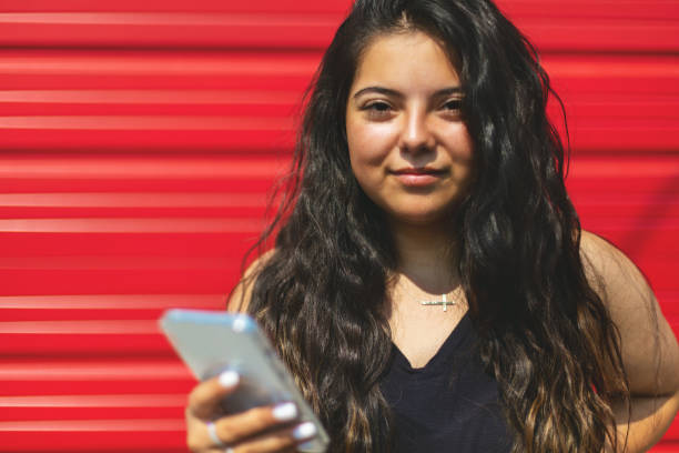 Hispanic Native American Generation Z Female Using Smart Phone Technology Standing In Front of Red Garage Door Urban Photo Series In Western Colorado Hispanic Native American Generation Z Female Looking at Camera Varying Expressions Urban Photo Series Hispanic Native American (Shot with Canon 5DS 50.6mp photos professionally retouched - Lightroom / Photoshop - original size 5792 x 8688 downsampled as needed for clarity and select focus used for dramatic effect) eyecrave stock pictures, royalty-free photos & images