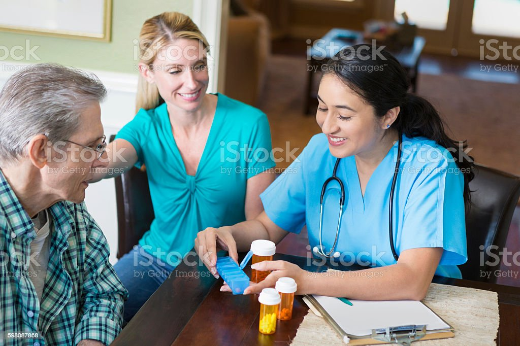 Hispanic nurse visits with senior patient in his home stock photo
