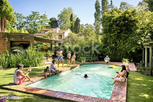Wide angle view of multi-generation family relaxing and watching children play and swim in backyard pool.