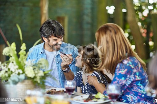 1196170672istockphoto Hispanic Parents Sitting with Young Daughter at Midday Meal 1192450773