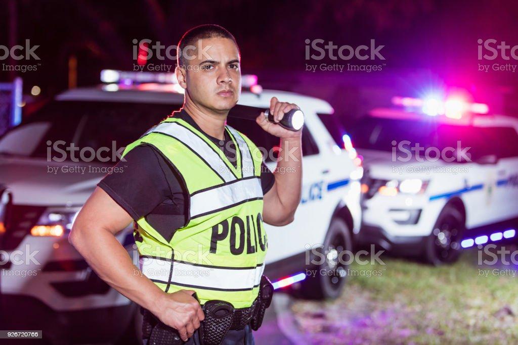 Hispanic police officer at night, flashing lights stock photo