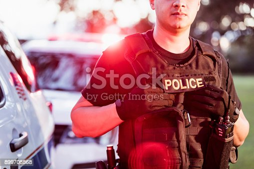 Cropped view of an Hispanic police officer wearing a bulletproof vest, standing beside two police cars. He is a mid adult man in his 30s.