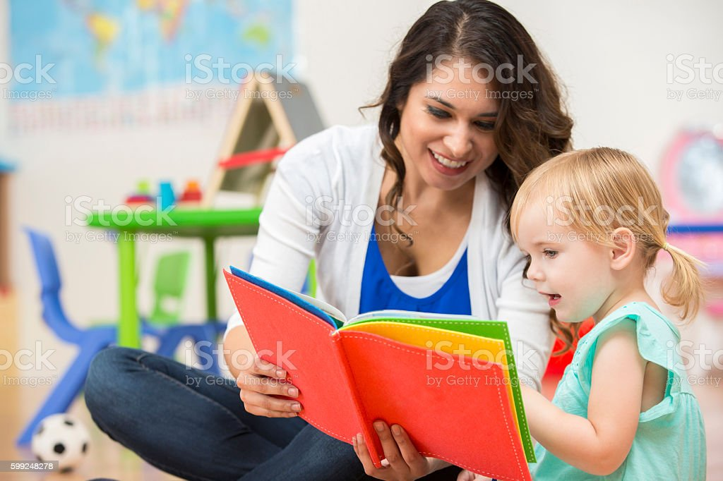 Hispanic Preschool Teacher Reading A Book To Cute Toddler Girl Royalty Free Stock Photo