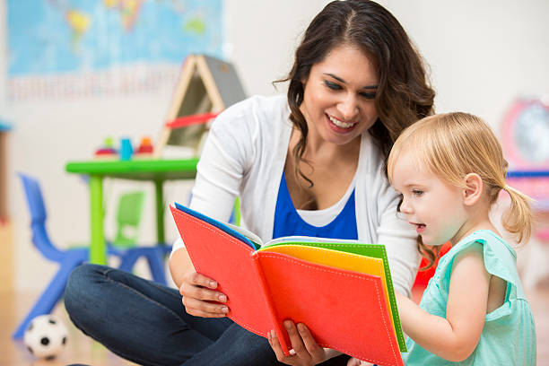 Hispanic preschool teacher reading a book to cute toddler girl stock photo