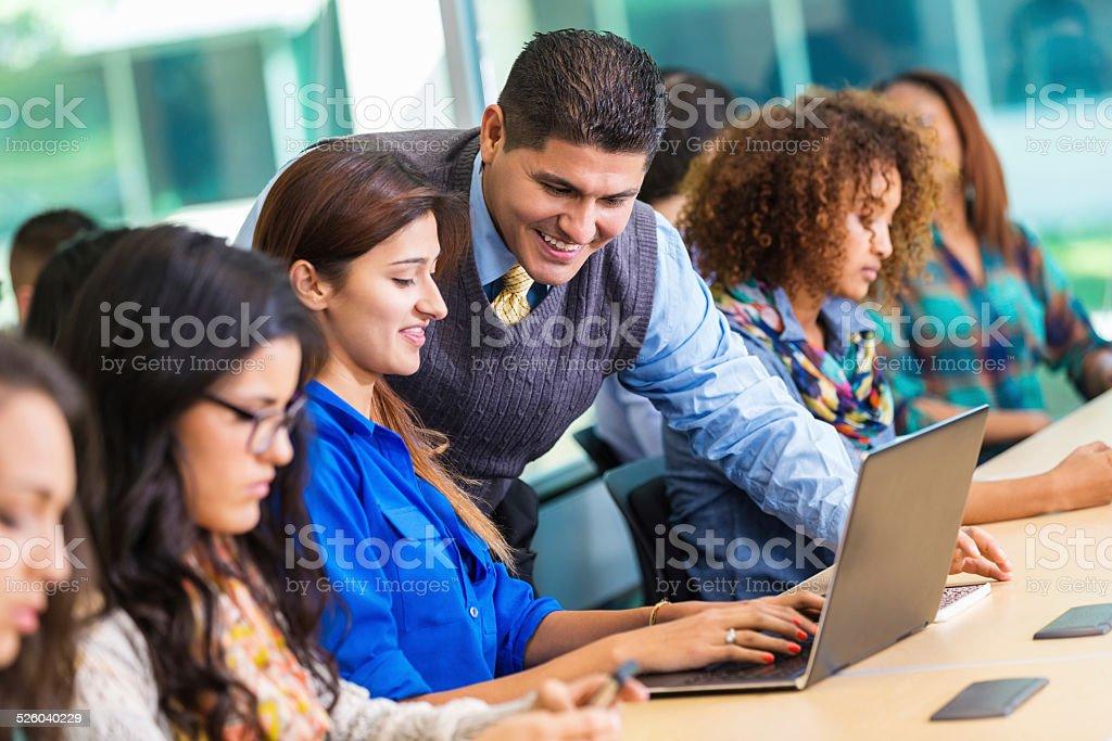 Hispanic professor helping student in busy college classroom stock photo