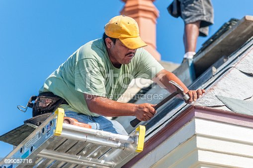 istock Hispanic Roofer Hammers a Copper Nail into a Piece of Slate Tile on the Roof 699087716