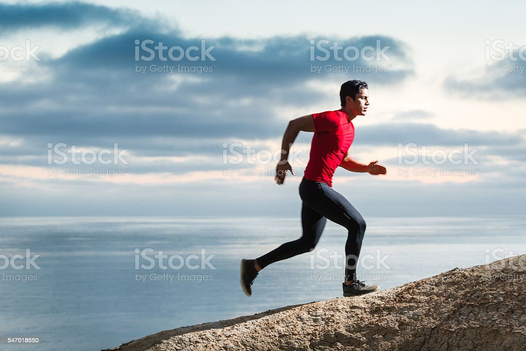 Hispanic Runner On The Bluffs Over The Ocean stock photo