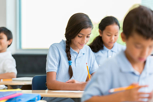 hispanic schoolgirl concentrates while working on class assignment - private school stock photos and pictures