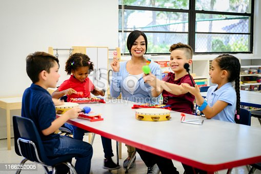 Smiling Hispanic schoolteacher sitting with elementary aged students at classroom table and playing musical instruments.