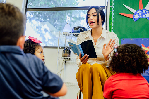 Young female Hispanic schoolteacher reading aloud to elementary aged students sitting around her on the floor.