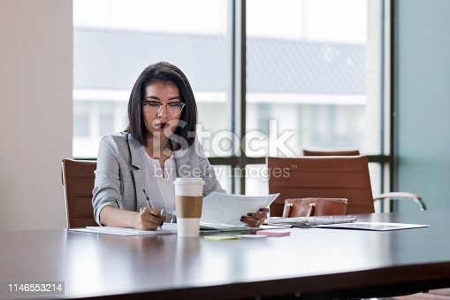 Taking some time after the meeting, the mid adult secretary prepares the time sheets for the month.