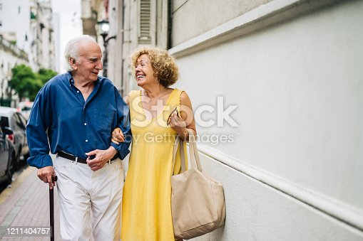 Front view of smiling active seniors in 70s and 80s arm in arm and talking as they walk down sidewalk in Buenos Aires.