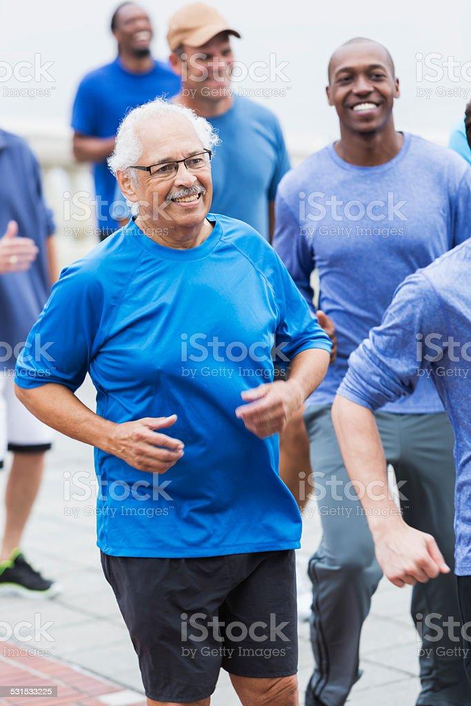 Hispanic senior man running with group stock photo