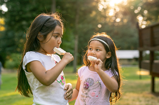 Adorable Hispanic sisters looking at each other while eating popsicles in the backyard of their home on a sunny and warm evening.