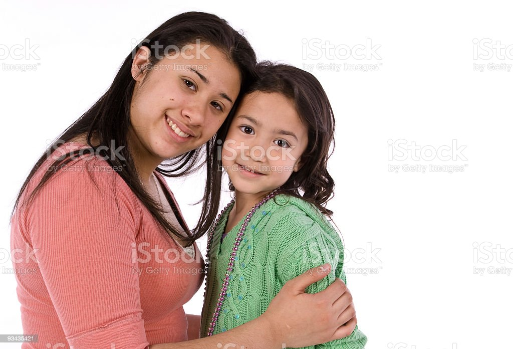 Hispanic sisters hugging stock photo