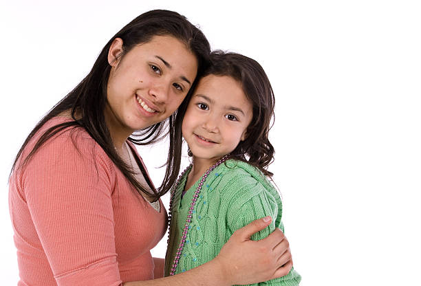 Hispanic sisters hugging stock photo