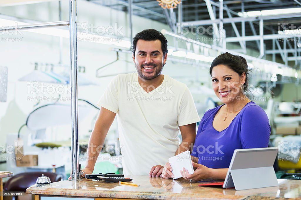 Hispanic small business owners, dry cleaner paying bills stock photo