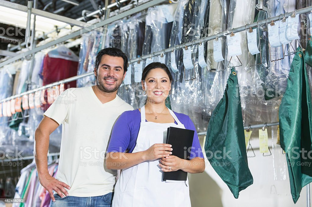 Hispanic small business owners of dry cleaning business stock photo