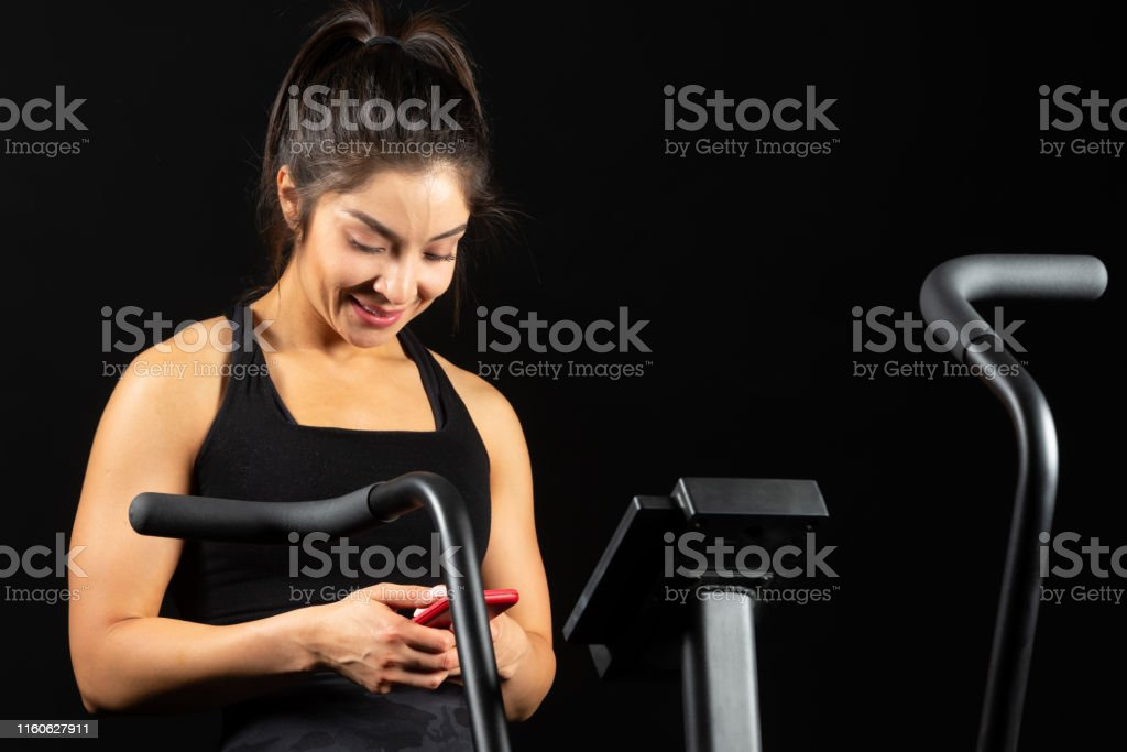 Smiling Hispanic sport trainer looking at her smart phone on black...