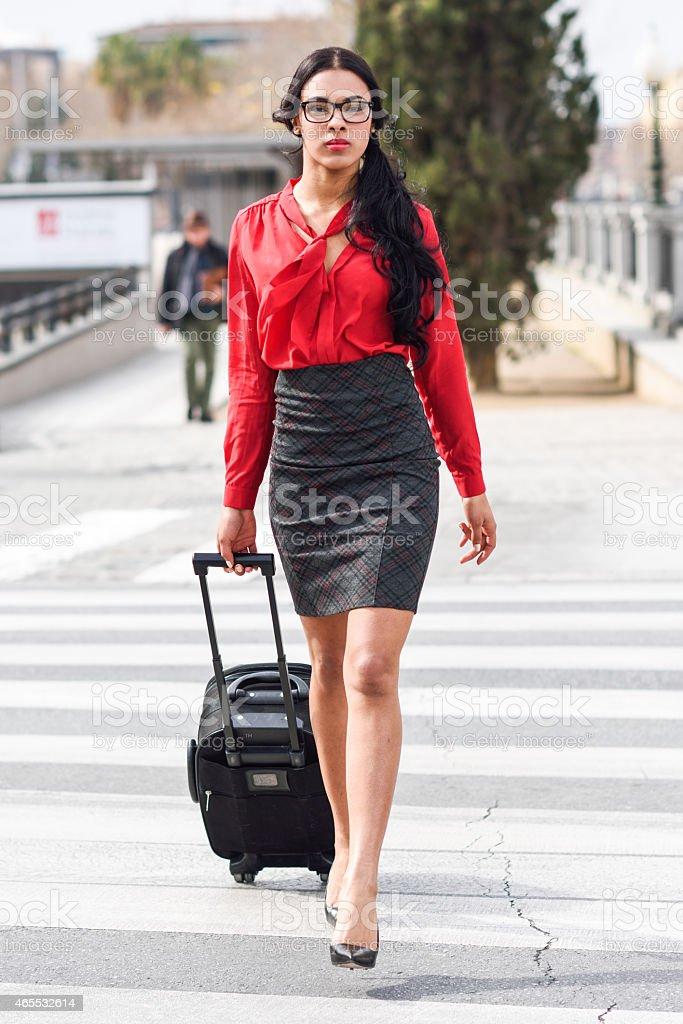Hispanic stewardess crossing street with luggage bags stock photo
