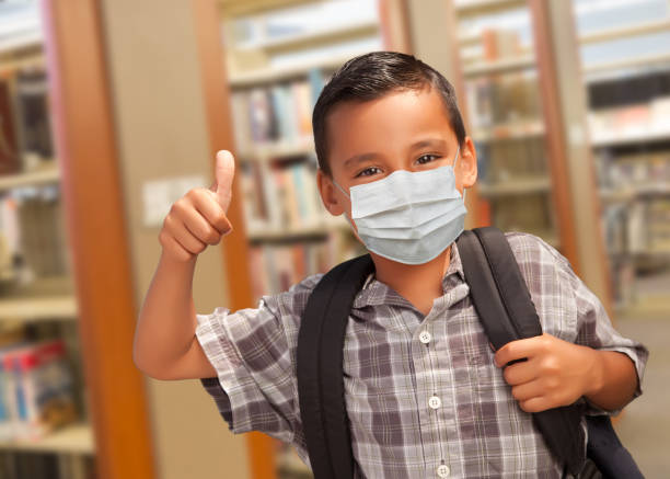 Hispanic Student Boy Wearing Face Mask with Thumbs Up and Backpack in the Library stock photo
