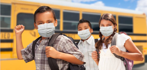 Hispanic Students Near School Bus Wearing Face Masks stock photo