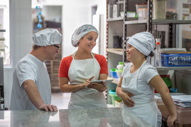 Hispanic Supervisor Using Tablet and Talking with Coworkers Close-up of female supervisor using digital tablet while discussing shift times with Down Syndrome coworkers in Argentine pasta factory. persons with disabilities stock pictures, royalty-free photos & images