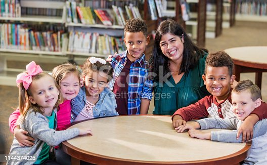 istock Hispanic teacher, elementary school children in library 1144374025