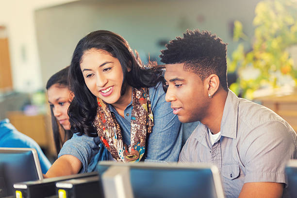 Hispanic teacher helping an African American teen with work. stock photo