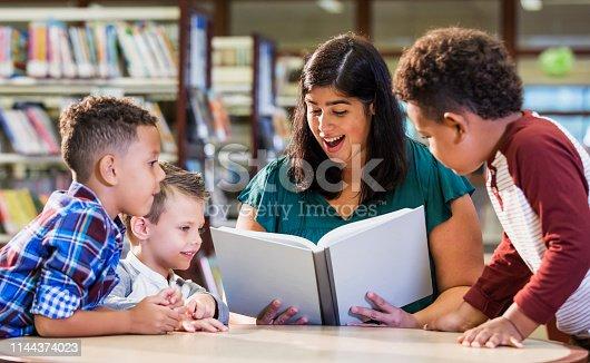 istock Hispanic teacher with three boys in library reading book 1144374023