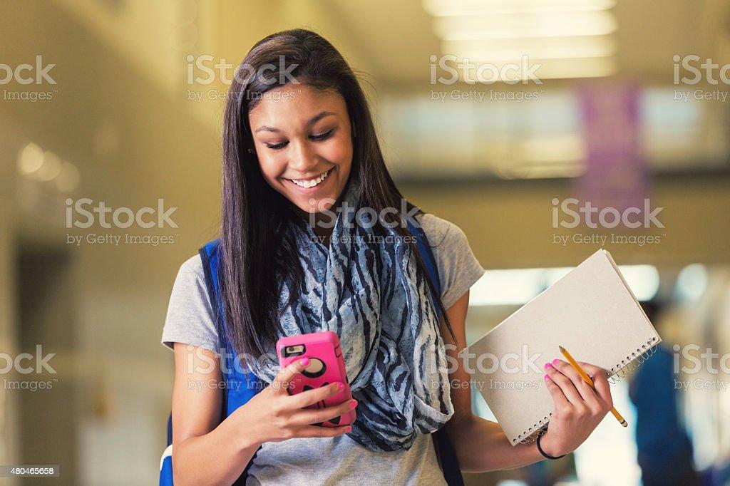 Hispanic teen high school student using smart phone in hallway