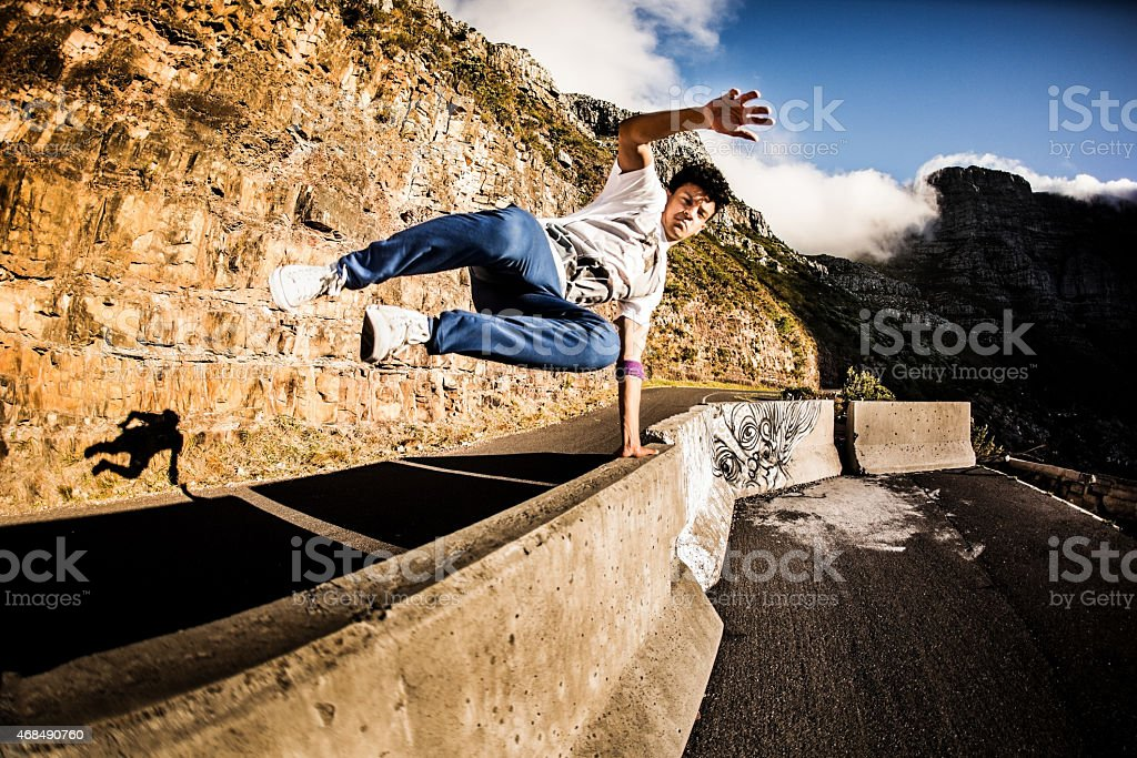 Hispanic teen jumping over a wall parkour style outdoors royalty-free stock photo