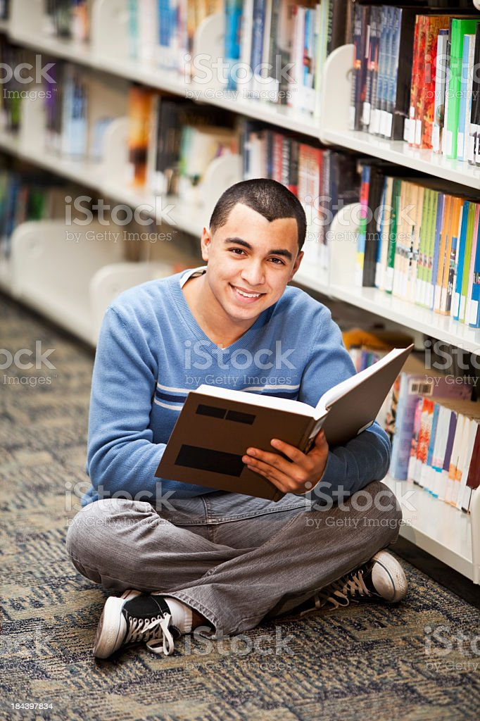 Hispanic teenage boy reading in library royalty-free stock photo