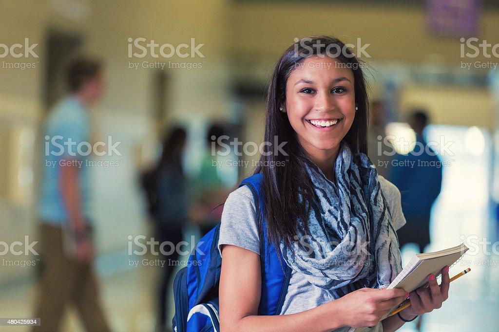 Hispanic teenage female high school student smiling in hallway stock photo