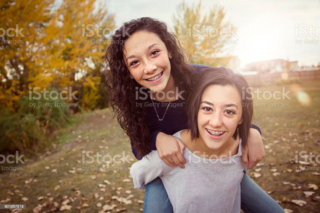 Hispanic Teenage girls having fun together outdoors стоковое фото