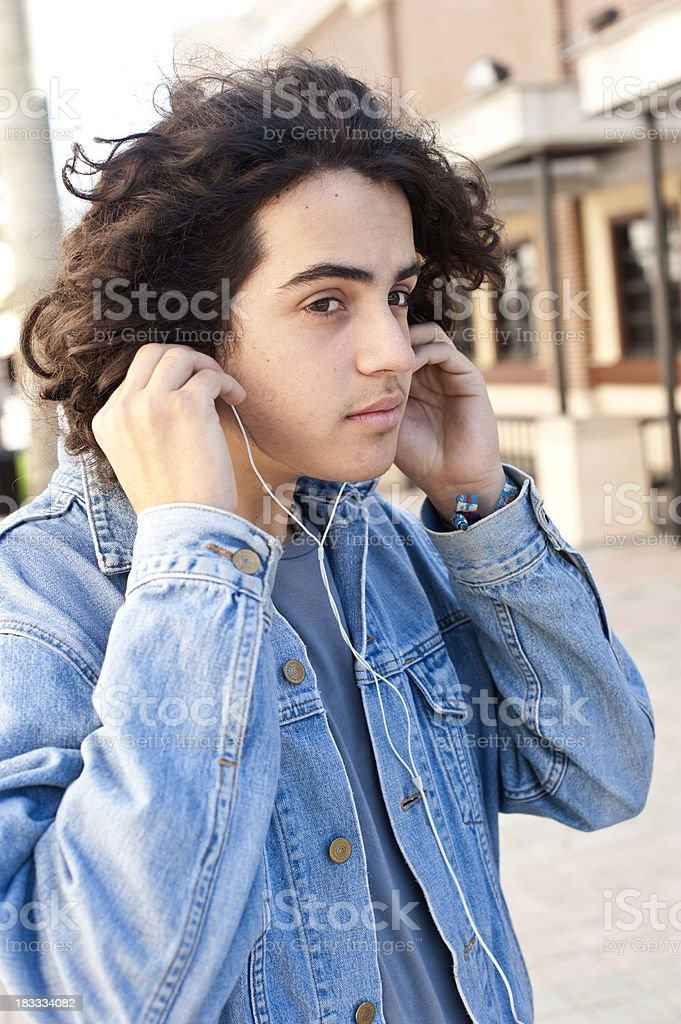 Hispanic teenager adjusting his headphone royalty-free stock photo