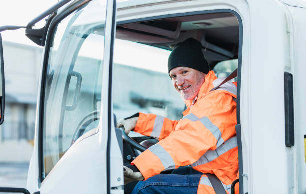 Hispanic truck driver sitting in vehicle, at warehouse stock photo