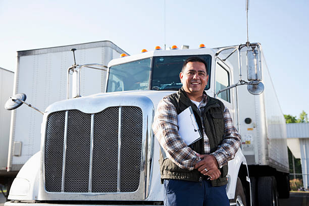 Hispanic truck driver with clipboard Hispanic truck driver (40s) standing in front of semi-truck with clipboard. driver occupation stock pictures, royalty-free photos & images