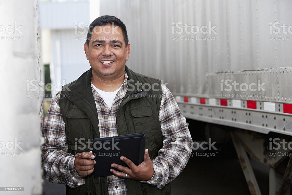Hispanic truck driver with digital tablet stock photo