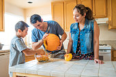 Hispanic US family carving pumpkin together. Mother, Father and Son