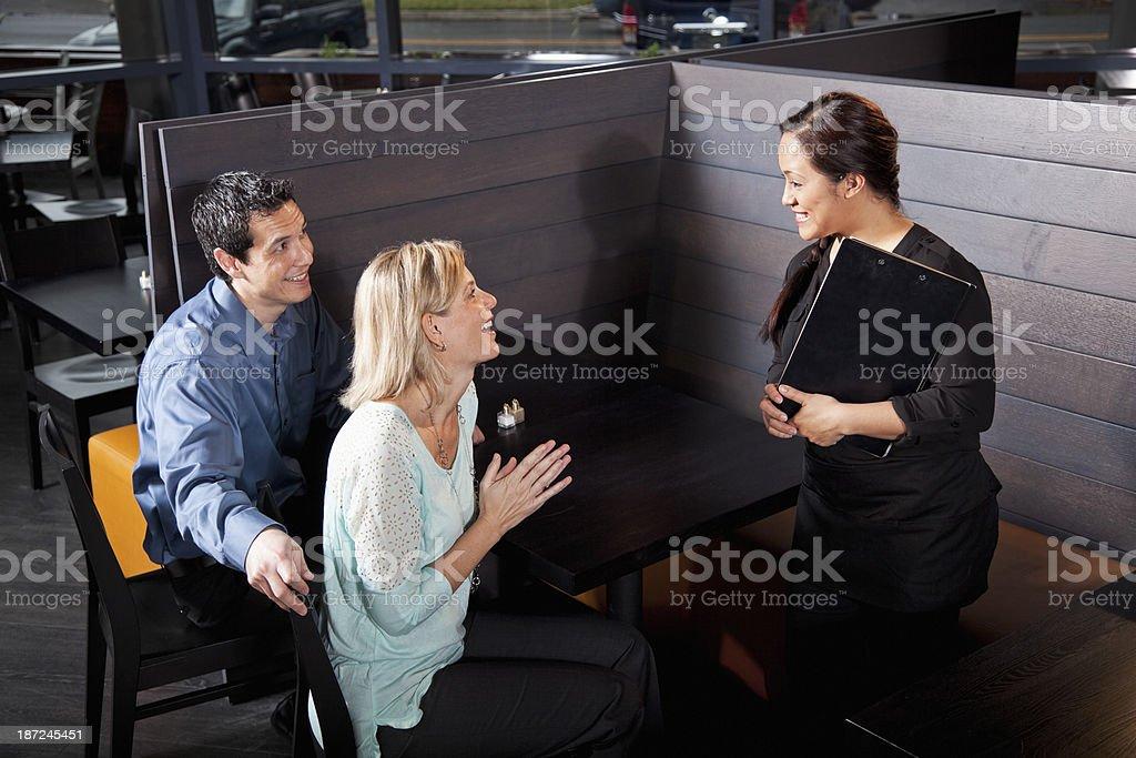 Hispanic waitress talking with customers royalty-free stock photo