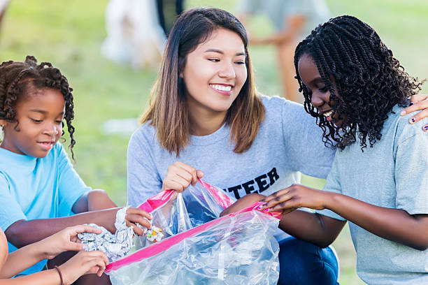 Hispanic woman and African American girls help with community cleanup - Photo
