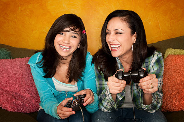 Hispanic Woman and Girl Playing Video game stock photo